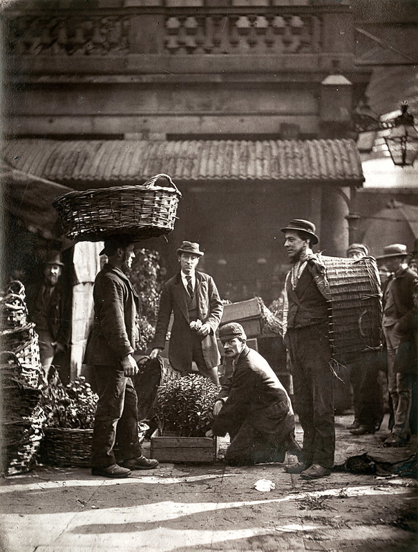 Black and white heritage photo of labourers at Covent Garden, tasked with carrying goods in baskets