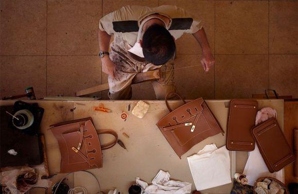 Un artisan assemblant un sac à main en cuir - Hermès