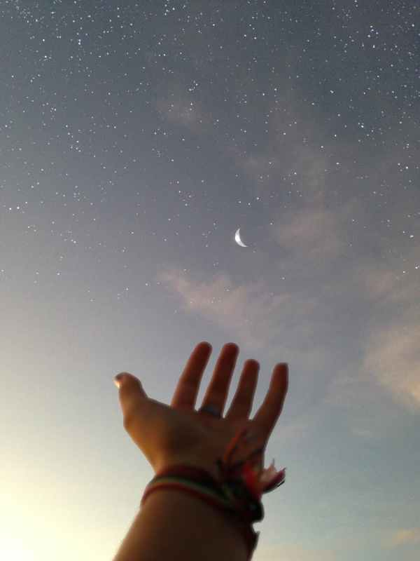 person s hand reaching for the sky