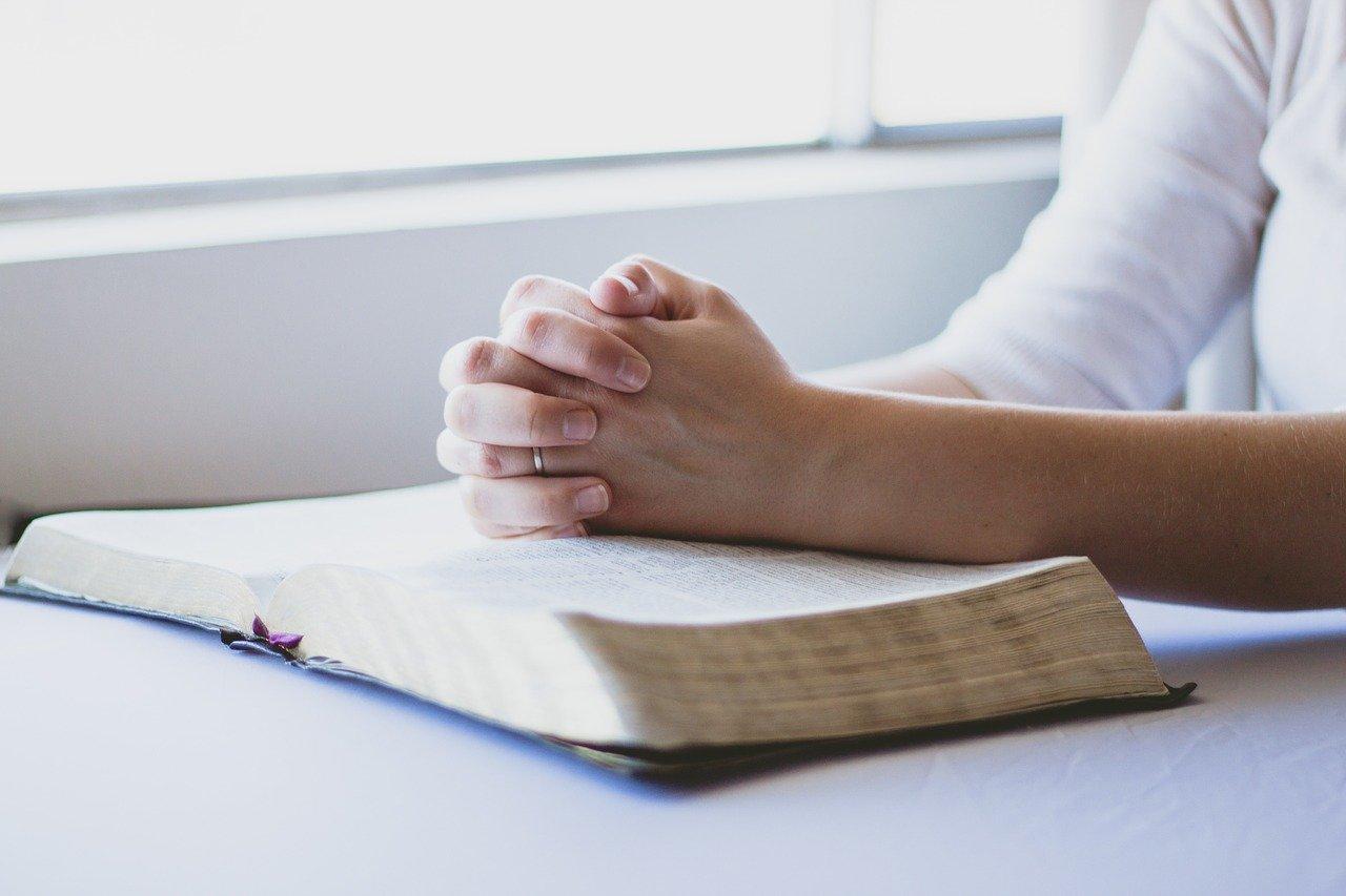 Mains jointes sur une bible