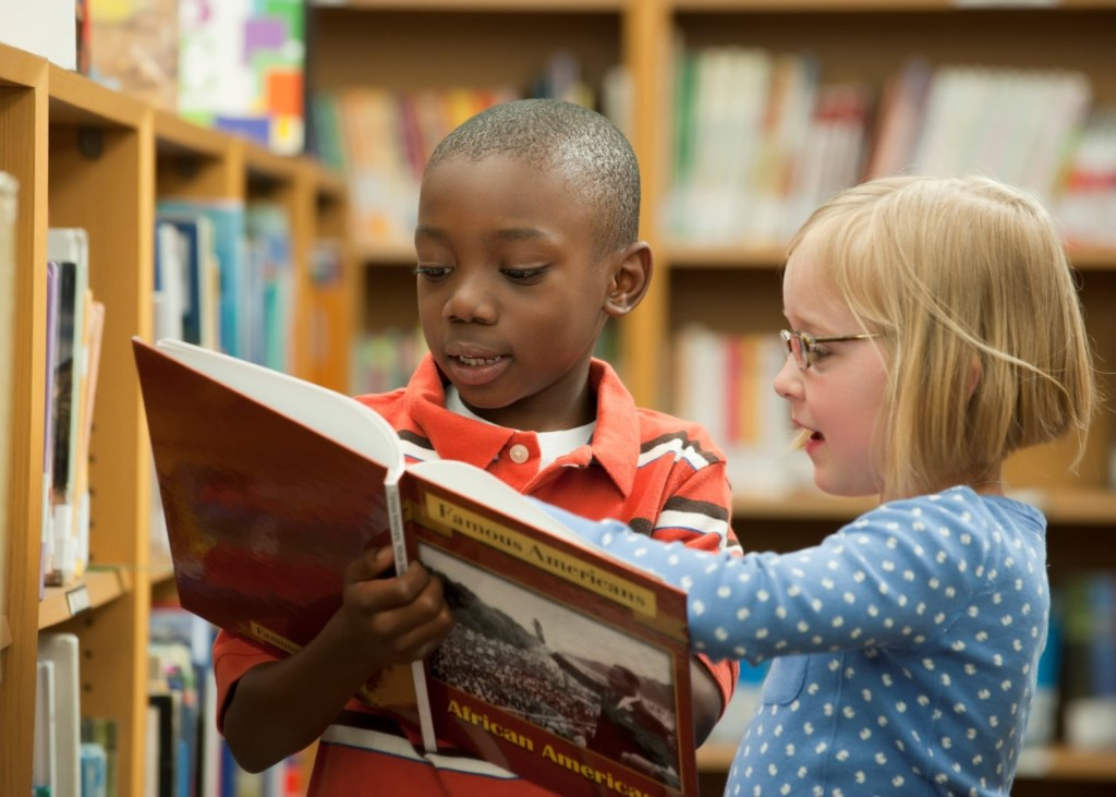 2 young students reading a book