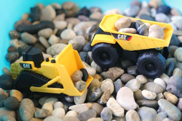 Mini construction vehicles and rocks come together to create this frugal and fun sensory bin | ParentalPerspective.com