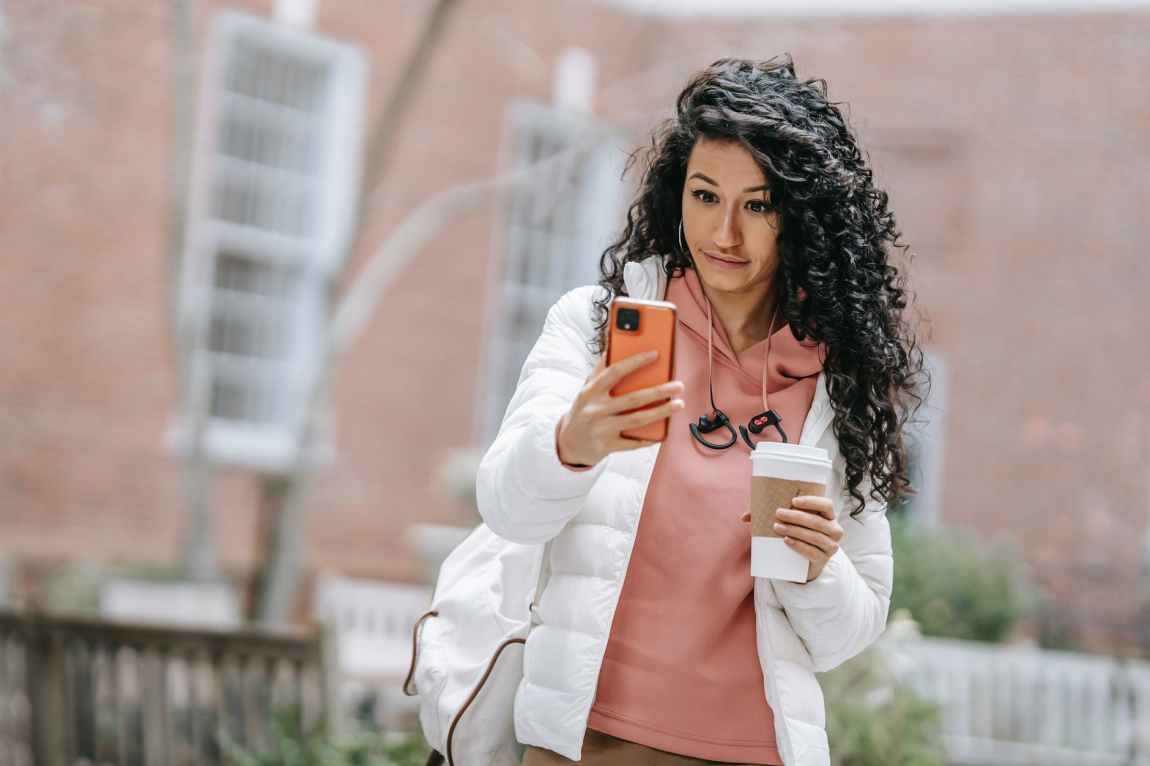 young ethnic female drinking takeaway coffee and using smartphone on street