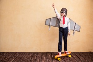 Portrait of young businessman with toy paper wings. Success, creative and startup concept. Copy space for your text