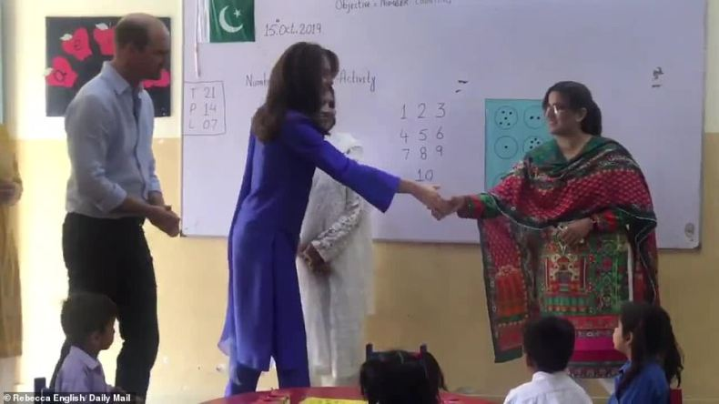 Hello! Kate shakes the hand of a teacher at the Islamabad Model College for Girls this morning as they prepare to speak to pupils