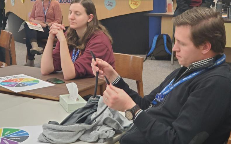 A Brainerd High School staff member examines a sweatshirt with strings meant for vaping during a staff meeting Wednesday, Jan. 22, with representatives from Crow Wing Energized there to spread awareness on the dangers and prevalence of vaping. Theresa Bourke / Brainerd Dispatch