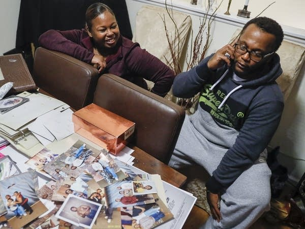 A man and woman sitting in front of a table with photos and papers.