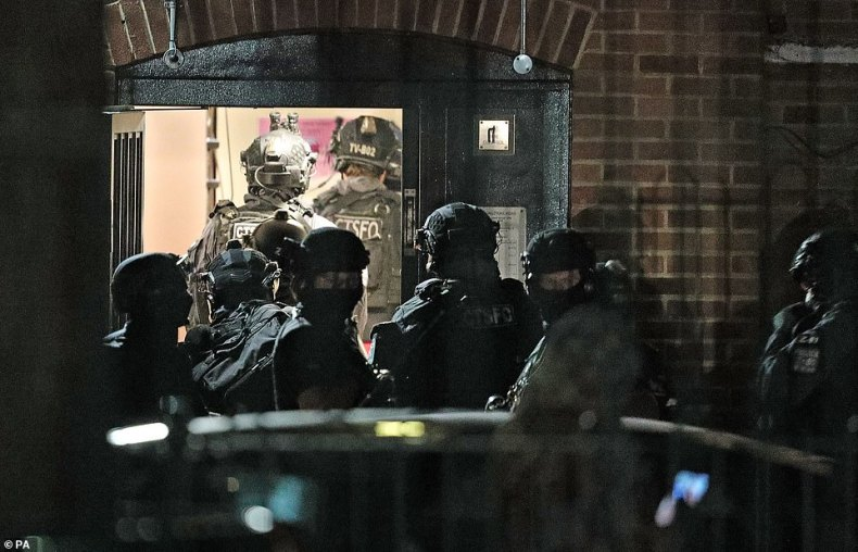 Armed officers entered the block of flats (pictured) at around 11pm on Saturday eveningcarrying semi-automatic weapons