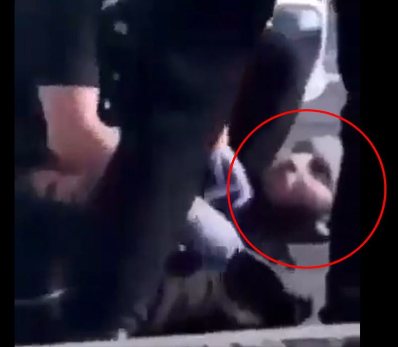 Capture: Mobile phone footage of a man, circled, on the floor as he is arrested by police