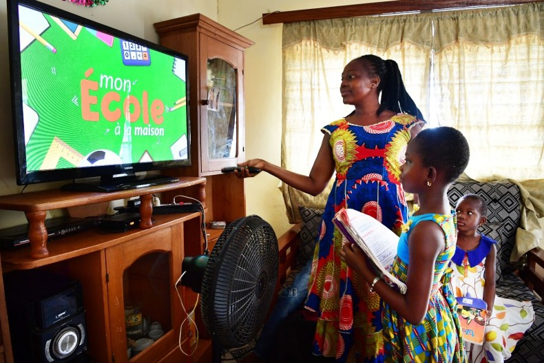 A mother helps her daughter Ange, 8, take classes on television at home