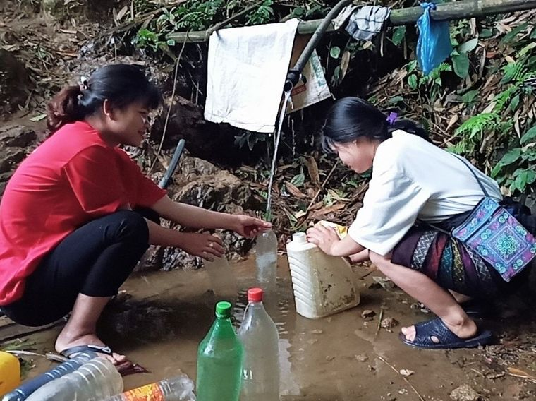 Two girls holding empty bottles over a stream of muddy water in Vietnam.