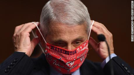 Dr. Anthony Fauci lowers his face mask as he prepares to testify before the Senate Health, Education, Labor and Pensions (HELP) Committee on Capitol Hill.