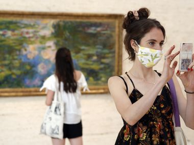 Libby Krueger of Fort Worth takes a photo of paintings in the Kimball Art Museum as her friend Kimberly Brubacher of Los Angeles views Claude Monet's Water-Lily Pond (1917-19) in Fort Worth, Tuesday, July 14, 2020. (Tom Fox/The Dallas Morning News)