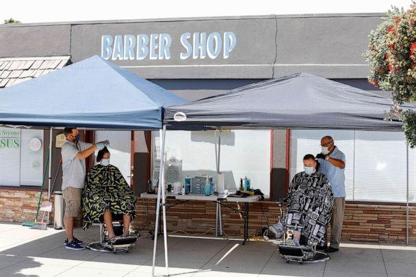 PHOTO: Barbers Nicolas Downs and Bob Castro cut customers hair from the sidewalk in front of Downs' barber shop during the outbreak of the coronavirus disease (COVID-19) in Solana Beach, Calif., July 21, 2020. (Mike Blake/Reuters)