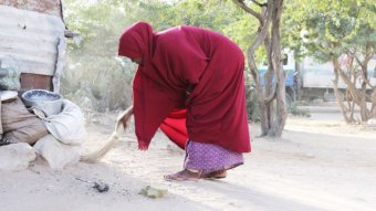 A woman wearing a red cape bends down to pick up something from the ground.