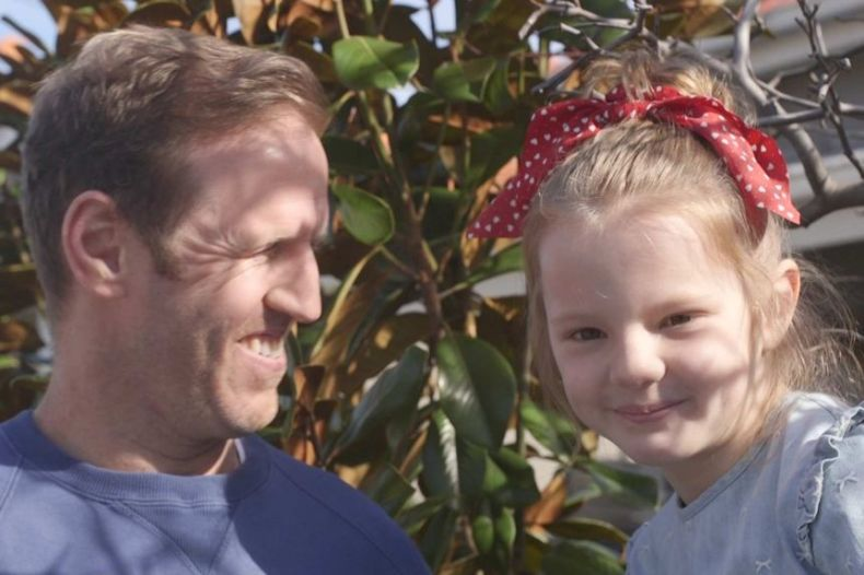 A father holding his smiling daughter who has a red bow in  her hair.