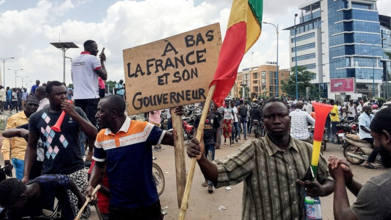 Opposition supporters react to the news of a possible mutiny of soldiers in the military base in Kati, outside the capital Bamako, at Independence Square in Bamako, Mali August 18, 2020. The sign read