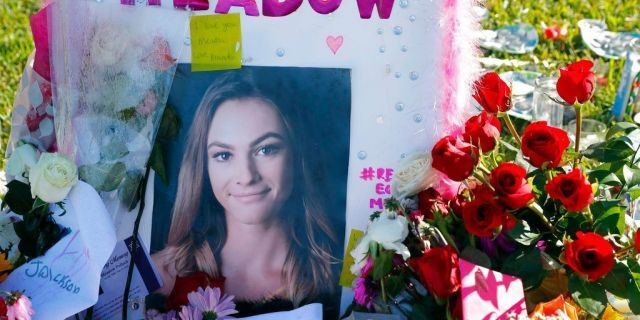 This Feb. 17, 2018, photo shows a photo of Meadow Pollack, one of the 17 victims who was killed in the Wednesday, Feb. 14, 2018, shooting at Marjory Stoneman Douglas High School, sitting against a cross as part of a public memorial, in Parkland, Fla. (AP Photo/Gerald Herbert)