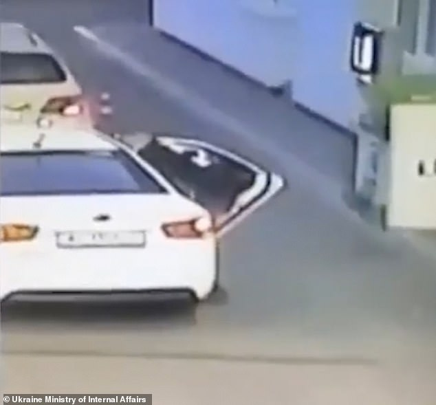 This is the moment the man places the youngster in the backseat of the white car in Boryspil, Ukraine
