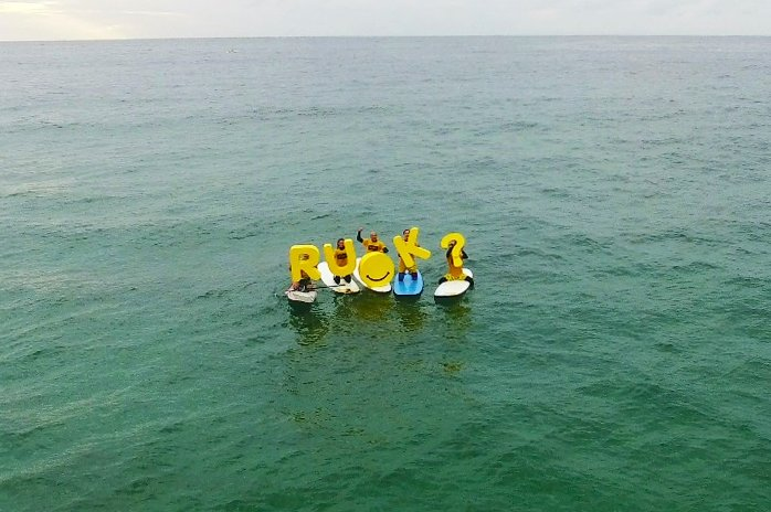 RUOK letters being held by people on surfboards