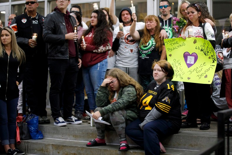 Devan Selvey's girlfriend Danielle, seated left, his sister Karissa, seated right, and mother Shari-Ann, centre holding candle, attend a vigil for the murdered teen outside Sir Winston Churchill Secondary School, in Hamilton, Ontario, on Wednesday, Oct. 9, 2019. (Cole Burston/CP)