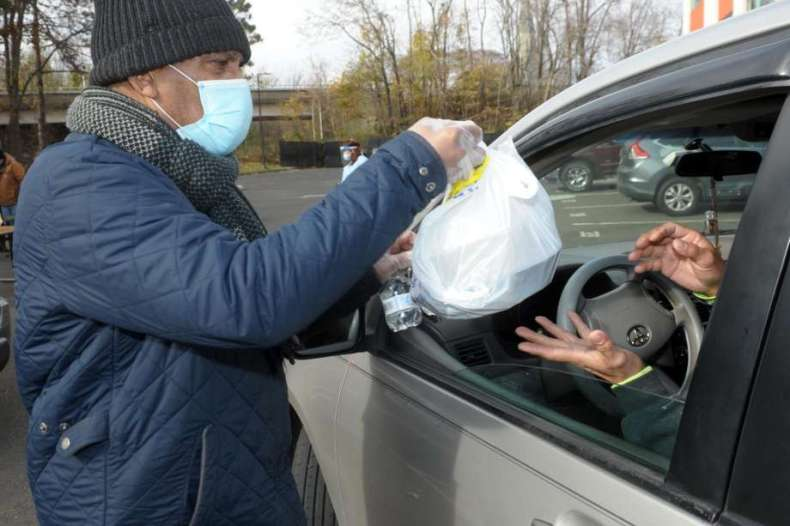 Lawrence Hudson from Career Resources delivers a boxed and bagged Thanksgiving meal to a waiting motorist during a food donation in Bridgeport, Conn. Nov. 19, 2020. The meals were provided by the Kennedy Center, and volunteers from Career Resources served the meals during the event. Photo: Ned Gerard / Hearst Connecticut Media / Connecticut Post