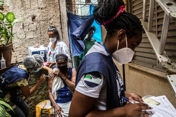 Justina Roberta Santos, 84, received a coronavirus vaccine during a campaign to inoculate older people with mobility issues, in Rocinha, Brazil, last month.