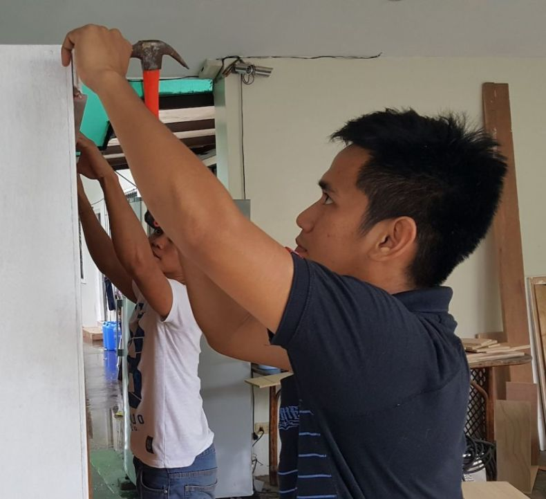 Teen boys and young men in the Second Chance program help build a door for use in the School of Life home in November 2017