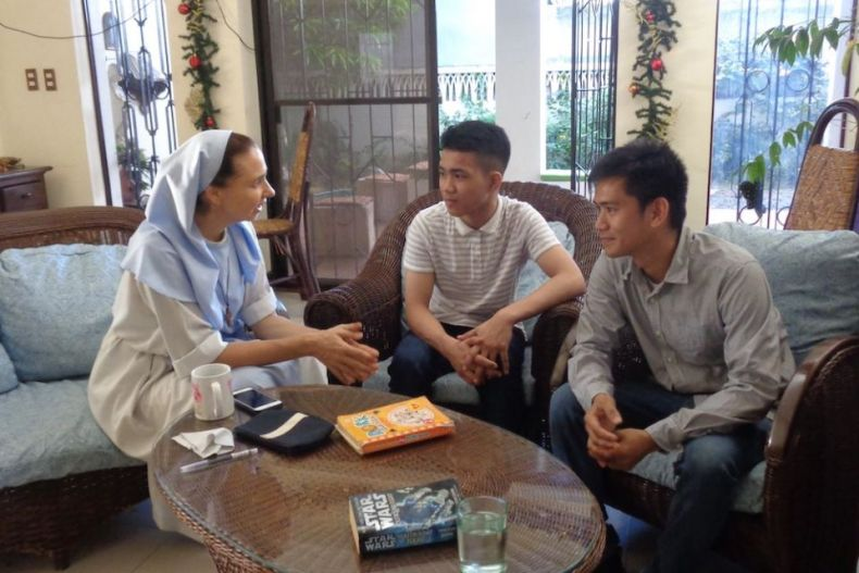 Catholic sister in a habit sits and talks to two young Filipino men