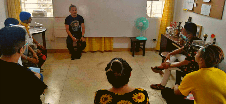 Young Filipino men sit in a circle indoors and discuss Second Chance program