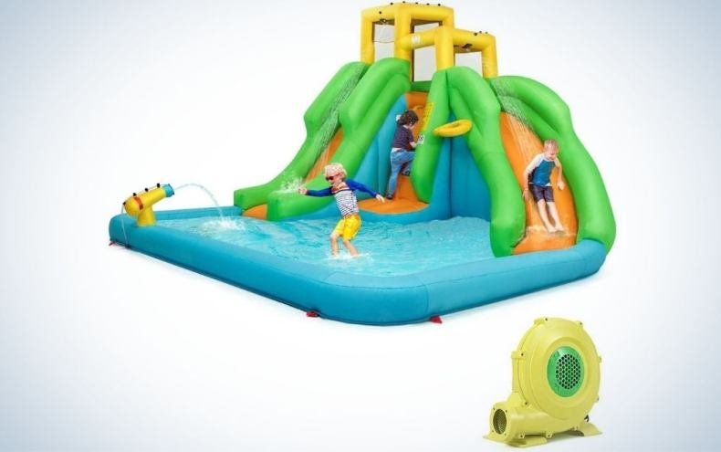Kids playing in a large blue splash pool with orange slides and full of water into it.