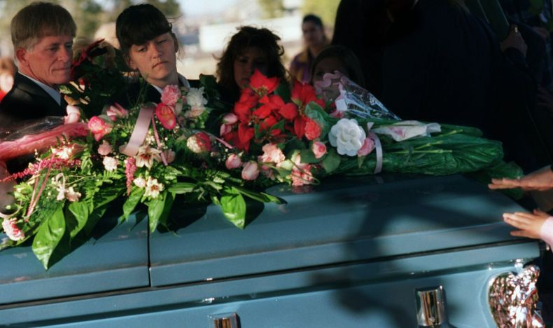 Amber Hagerman's parents lay a rose  on Amber's casket as they leave graveside services on Jan. 20, 1996 in Arlington.