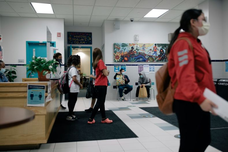 Students walk through the lobby of P.S. 89, with ornate murals on the walls and light blue doors.