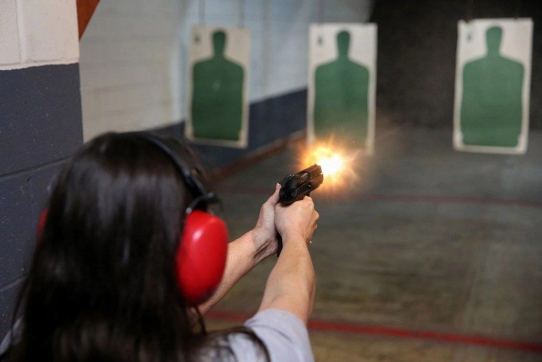 A woman shoots at a Texas gun range in 2018. Federal authorities say you can use medical marijuana or own a gun but that you can't do both.