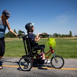 Trista Sterner, left, gives a push as her daughter, Audrey Sterner, 13, rides her new adaptive tricycle at Germania Park in Murray on Wednesday, July 21, 2021. Sterner received the trike from a partnership between Wasatch Adaptive Sports, The Hartford and Move United.