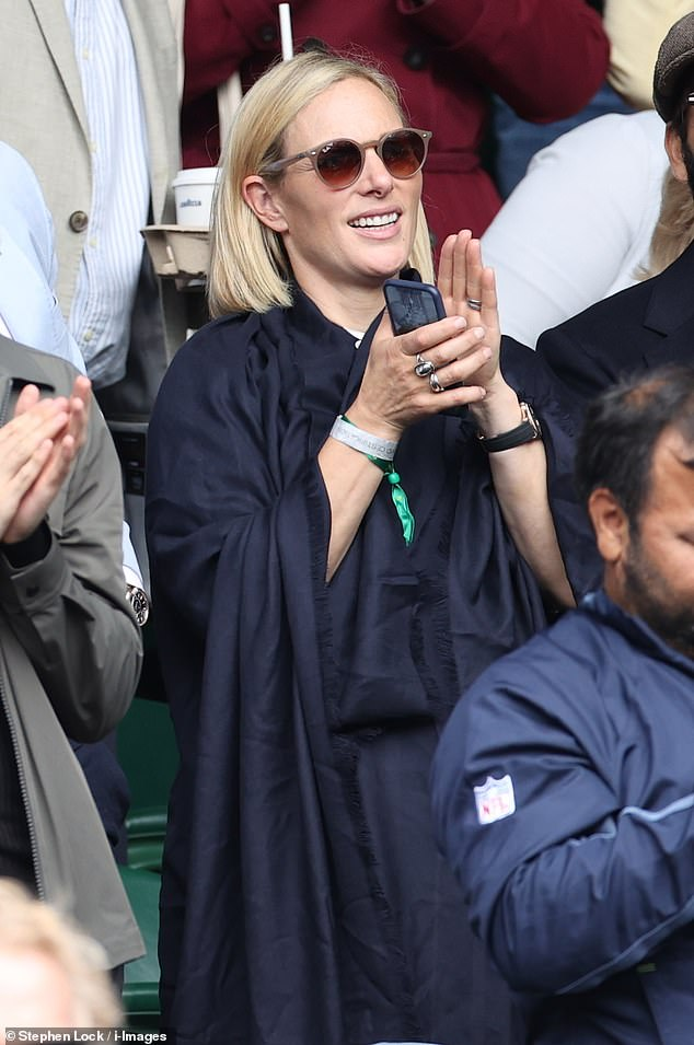The Queen's granddaughter clutched her phone in her hand as she stood to applaud the performance on centre court