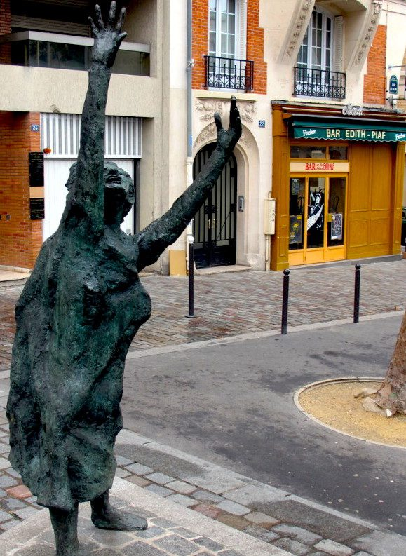 "This contemporary statue representing ""the little bird"" is situated on Place Edith Piaf in Paris, with a bar in her honor just behind it. Image credit: <a href= http://photokris.over-blog.com/article-madame-edith-piaf-91799523.html"">Photokris-overblog.com<a>"