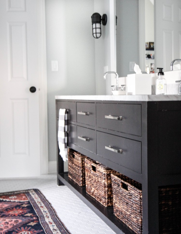 black bathroom vanity with vintage rug