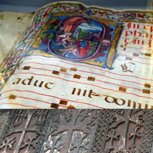 illuminated manuscript detail of O and row of carved stone crosses