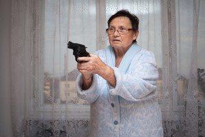 Scared senior woman aiming a gun indoors.