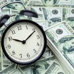 reloj despertador y billetes de cien dolares