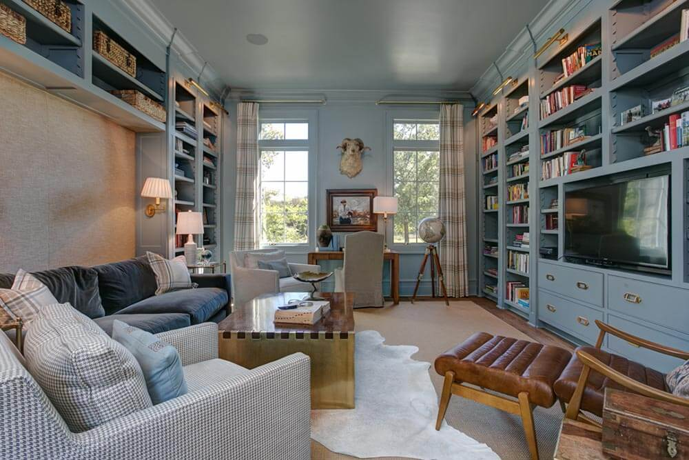 Blue-grey library with comfy suede and leather furniture. The library has an old-world mixed with contemporary feel.