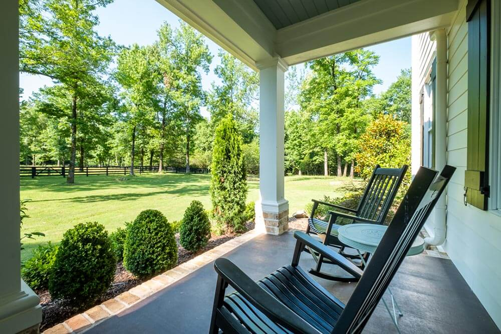 Front porch looking over green country acreage