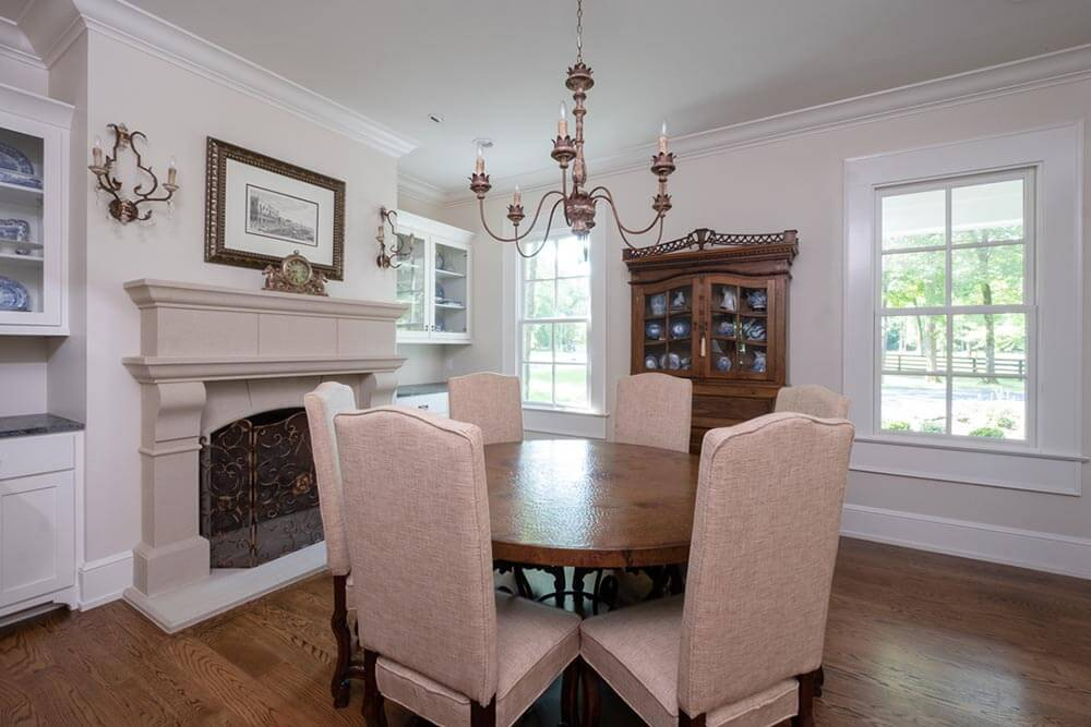 Strong, elaborate fireplace in a small dining room with classic furniture
