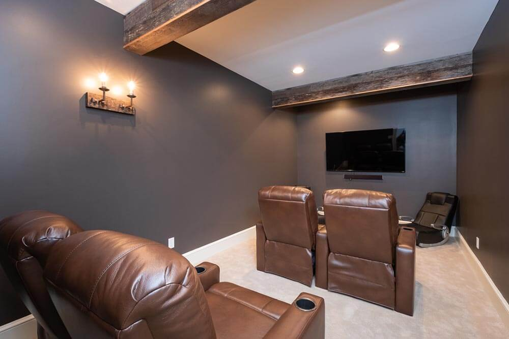 dark colored theater room with two large exposed beams and some unique industrial pipe lighting