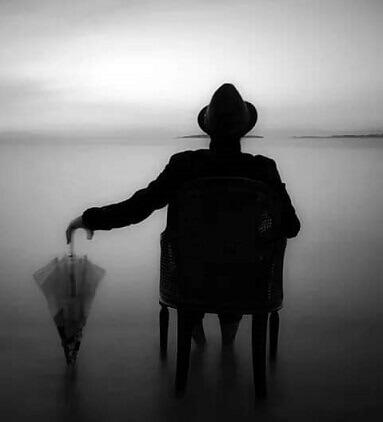 Şemsiyeli oturan adam