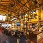 Un gran restaurante, con mesas altas y bajas, y una divertida barra de bar