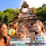 La pirámide maya de 46 pies de alto desde la que cae agua es la atracción principal de la piscina Dig Site en Disney's Coronado Springs Resort. Niños sonrientes sentados en los escalones de la pirámide maya en la piscina Dig Site
