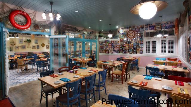 Redes de pescar desechadas, timones de barco de madera y fotos de los socios de Disney Vacation Club y sus familias cubren las paredes, pero no es necesario decir que todos son bienvenidos a Olivia's Café, abierto todos los días para el desayuno, el almuerzo y la cena. Área de asientos alternativa con paredes cubiertas de parafernalia y fotos de navegación