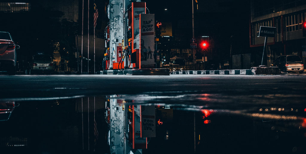 Cars at petrol station at night in the rain